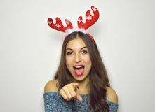 Surprised excited christmas woman on gray background. Beautiful happy christmas girl with reindeer horns on her head. Stock Images
