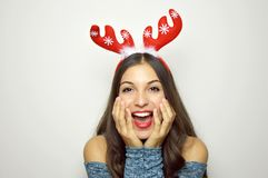 Surprised excited christmas woman on gray background. Beautiful happy christmas girl with reindeer horns on her head. Royalty Free Stock Photo