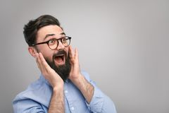 Surprised and excited man. Bearded man in glasses feeling surprised and excited on gray background Stock Photos