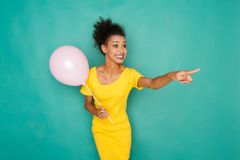 Excited mulatto girl at studio background. Surprised and excited mulatto girl pointing on something. Smiling woman in bright yellow dress at azur studio Stock Photos
