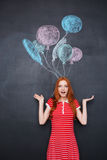 Surprised excited woman standing over chalkboard background with drawn balloons Royalty Free Stock Photos