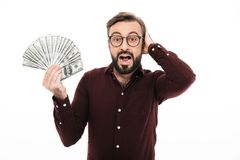 Surprised excited young man standing isolated. Photo of surprised excited young man standing isolated over white background. Looking camera holding money Royalty Free Stock Image