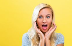 Surprised young woman posing on a solid background. Surprised and excited young woman posing on a solid background Stock Photography