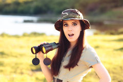 Surprised Explorer Girl with Camouflage Hat and Binoculars Stock Photo