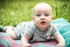 Surprised expression baby looking to camera. Surprised expression baby outdoors in summer Royalty Free Stock Image