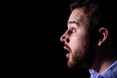 Surprised face in the dark. Bearded man looking surprised into the dark Royalty Free Stock Photo