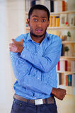 Surprised face of a man holding his shoulder, big eyes and raised eyebrows Stock Photo