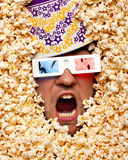 Surprised face in popcorn watching 3D movie. Surprised face in popcorn with bucket on head watching 3D movie royalty free stock photo