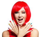 Surprised face of  pretty woman  with  red hair and multicolor n. Surprised face of an young pretty woman  with bright red hairs and multicolor nails.  Studio Royalty Free Stock Image