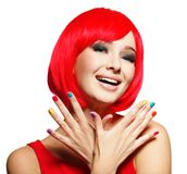 Surprised face of  pretty woman  with  red hair and multicolor n. Surprised face of an young pretty woman  with bright red hairs and multicolor nails.  Studio Stock Images
