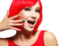 Surprised face of  pretty woman  with  red hair and multicolor n. Surprised face of an young pretty woman  with bright red hairs and multicolor nails.  Studio Royalty Free Stock Images