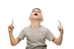 Surprised fair-haired boy in a gray T-shirt stands and points with the index fingers up. Isolate on white background.  stock photo