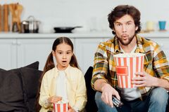 Surprised father and daughter watching movie and holding buckets of popcorn at home.