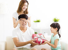 Surprised Father receiving gift box from wife and daughter Stock Photos