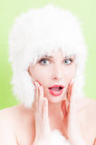Surprised female with blue eyes wearing fur hat. Isolated on green background Stock Photos