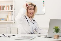 Surprised doctor with glasses sitting at desktop Royalty Free Stock Images