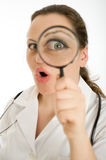 Surprised female doctor with magnifying glass Stock Photos
