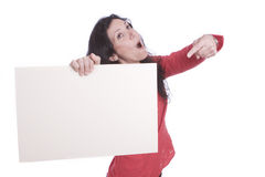 Surprised female holding and pointing a white card. Portrait of a surprised female holding and pointing a blank white card, over a white background Stock Photography