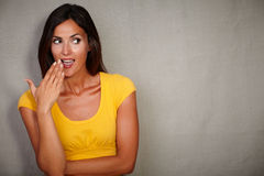 Surprised female looking away with hand to mouth Stock Image