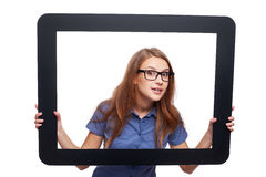 Surprised female peeping out of tablet frame Stock Photos