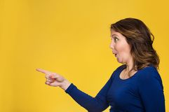 Surprised female pointing out at copy space stock photo