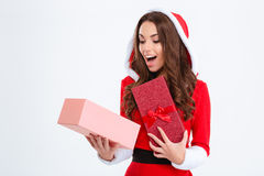 Surprised female in santa claus costume looking inside present box Royalty Free Stock Image