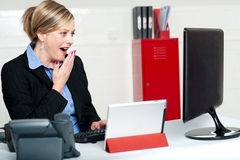 Surprised female secretary looking at lcd screen Stock Photo