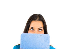 Surprised female student hiding face behind clipboard Royalty Free Stock Images