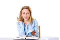 Surprised female student read book, isolated. Surprised or stressed attractive female student reads book, studio shoot isolated on white Royalty Free Stock Images