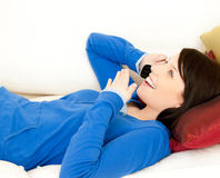Surprised female teenager phoning on a sofa Stock Photo
