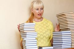 Surprised fifty-year-old woman in a yellow sweater and a lot of books stock images