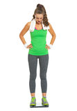 Surprised fitness young woman standing on scales Stock Photography