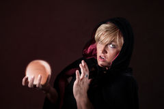 Surprised Fortuneteller. Caucasian female fortuneteller wearing black viel holds crystal ball over maroon background Stock Photography