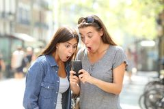 Surprised friends finding online content in a phone. Two surprised friends finding online content in a smart phone in the street Stock Images