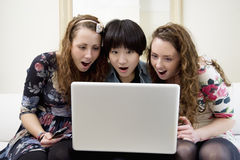 Surprised friends looking at something in laptop Royalty Free Stock Photos