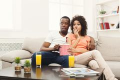 Surprised african-american young couple watching TV at home. Surprised and frightened african-american couple relaxing and watching TV at home, having rest after Stock Image