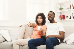 Surprised african-american young couple watching TV at home. Surprised and frightened african-american couple relaxing and watching TV at home, having rest after Stock Images