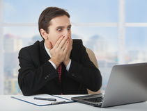 Surprised  frightened businessman with laptop Stock Photo