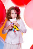 Surprised frightened girl in the hat of a large bow on a backgro Royalty Free Stock Photography
