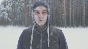 Surprised frozen man with glasses in the snow looking at the camera in the winter forest after a snow storm. Immunity and cold Royalty Free Stock Photography