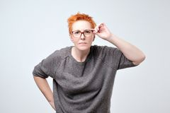 Surprised frustrated mature woman with red hair. She has problems with eyesight. She straightens her glasses trying to see the text stock photos