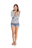 Surprised full length woman. Full length of surprised young stylish slim female in denim shorts  holding her head in amazement and open-mouthed, isolated on Stock Image