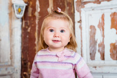 Surprised funny blond little girl with big grey eyes. And plump cheeks looks up. Studio portrait on grunge wooden background Royalty Free Stock Photos
