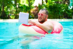 Surprised Funny fat male in pink glasses on an inflatable circle in the pool works on a laptop portraying a girl. stock photo