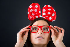 Surprised funny girl looking up. Surprised girl with a big hair bow and glasses looking up. Close-up portrait, dark background Royalty Free Stock Image