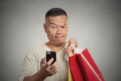 Surprised funny man holding red shopping bags looking at smart phone royalty free stock photo
