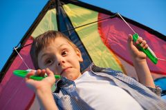 Surprised funny small boy with a kite on his shoulders stock photo