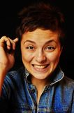 Surprised funny woman. A beautiful brunette girl with a short   hair in blue jeans jacket sitting in front of black background and funny smiling. Her face is Royalty Free Stock Photos