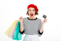 Surprised ginger woman with packages holding credit card. And looking at the camera over grey background royalty free stock photo