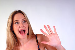 Surprised girl. Young blonde girl looking surprised with hand upraised with fingers spread. Shot against a white background with space  for text upper right Stock Images